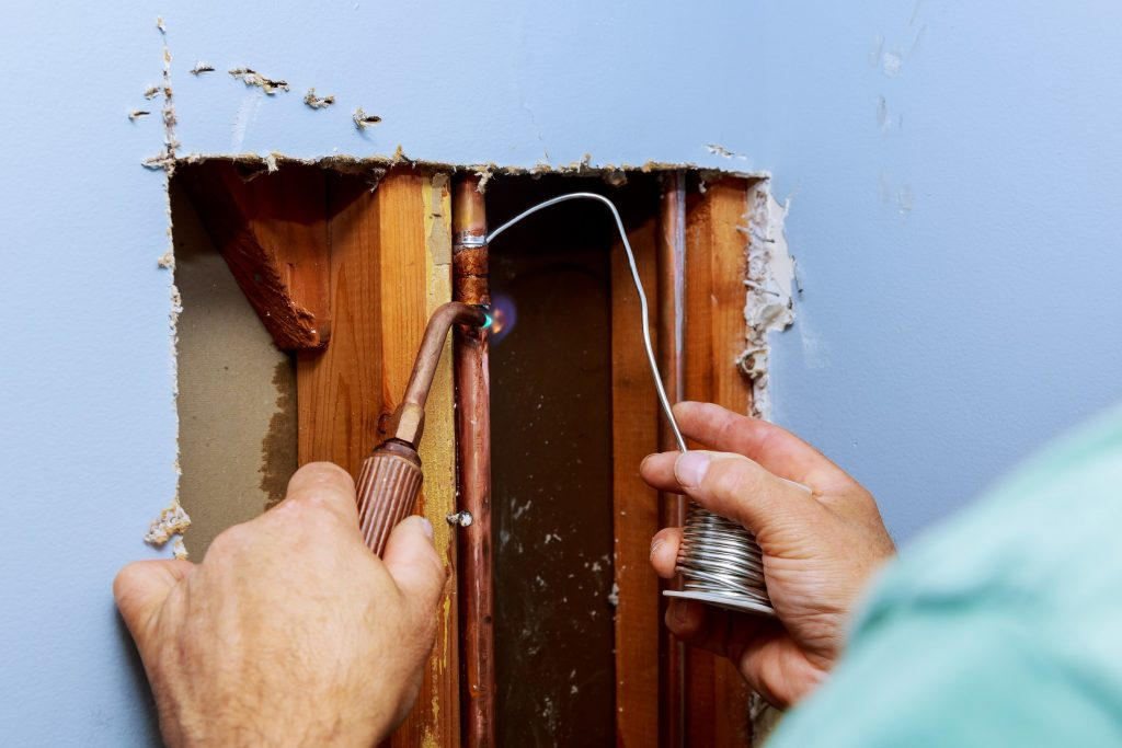 Fixing metal pipes and fittings in a wall from leaking